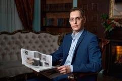 L'homme d'affaires dans un costume lit un journal près de la cheminée images stock