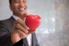 l'homme d'affaires dans un costume montre le grand coeur rouge au wor de bureau Images stock