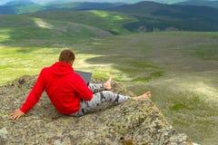 L'homme d'affaires dans un pull molletonné rouge s'assied sur une roche sur un mounta photographie stock libre de droits