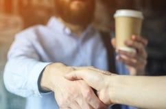 L'homme d'affaires dans une chemise bleue boit du café et salue la main avec un associé Concept de pause-café images stock