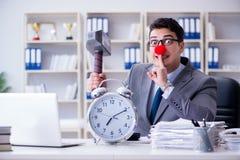 L'homme d'affaires de clown dans le bureau avec le marteau et un réveil Photo stock