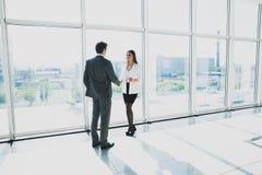 L'homme d'affaires de deux jeunes et la femme d'affaires se tiennent dans le bureau moderne avec les fenêtres panoramiques Photographie stock