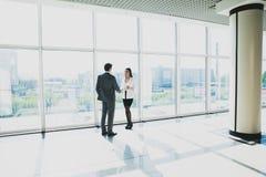 L'homme d'affaires de deux jeunes et la femme d'affaires se tiennent dans le bureau moderne avec les fenêtres panoramiques Photos libres de droits