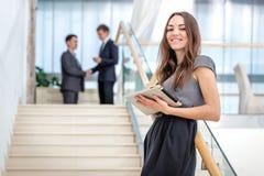 L'homme d'affaires de femme se tient sur les escaliers regardant l'appareil-photo Soyez Photographie stock