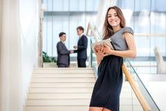 L'homme d'affaires de femme se tient sur les escaliers regardant l'appareil-photo Soyez Image stock