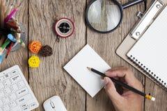 L'homme d'affaires de main écrivent sur la note de livre blanc avec l'objet d'affaires photographie stock libre de droits
