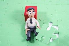 L'homme d'affaires de pâte à modeler rassemble un puzzle photographie stock libre de droits