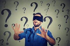L'homme d'affaires de portrait a bandé les yeux à étirer ses bras marchant par beaucoup de questions Photo stock