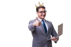 L'homme d'affaires de roi jugeant un ordinateur portable d'isolement sur le fond blanc photographie stock