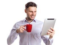 L'homme d'affaires de sourire bel Holding Red Cup et lit l'ordinateur Photos stock
