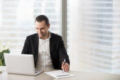 L'homme d'affaires de sourire heureux dans le bureau regardant l'ordinateur portable sreen Image stock