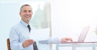 L'homme d'affaires de sourire réussi avec des documents s'assied sur Image stock