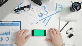 L'homme d'affaires de vue supérieure s'asseyant au bureau remet près de l'orientation horizontale de téléphone intelligent vert d banque de vidéos