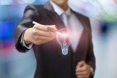 L'homme d'affaires dessine une ampoule photos libres de droits