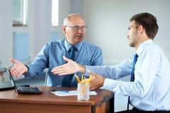 L'homme d'affaires deux avec l'ordinateur portatif discutent quelque chose Photographie stock