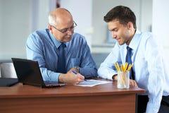 L'homme d'affaires deux discutent quelque chose, pousse de bureau Photographie stock libre de droits