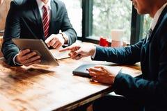 L'homme d'affaires deux reposant et regardant le comprimé, ils se réunissent au sujet du plan d'action, du marketing et de financ photo stock