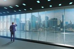 L'homme d'affaires devant la fenêtre de bureau pensant à de nouveaux défis images libres de droits