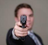 L'homme d'affaires dirige le canon avec la profondeur de la zone image libre de droits