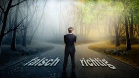 L'homme d'affaires doit décider quelle direction est meilleure avec le ` de mal de ` de mots et ` de ` le bon sur la route Photographie stock libre de droits