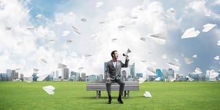 L'homme d'affaires en parc d'été annonçant quelque chose en haut-parleur et papier surface le vol autour Image stock
