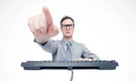 L'homme d'affaires en verres repose à une table avec des points d'un clavier un doigt à vous, sur le fond clair orientation vers  photo stock