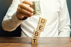 L'homme d'affaires enl?ve les blocs en bois avec la dette de mot La r?duction de cr?ance ou l'annulation est la r?mission partiel image libre de droits