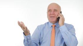 L'homme d'affaires entend nouvelles financières de téléphone de bonnes et fait des gestes de main enthousiastes photographie stock libre de droits