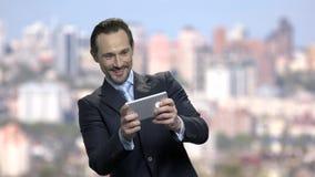L'homme d'affaires enthousiaste joue le jeu mobile banque de vidéos