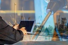 L'homme d'affaires est contrôle utilisé de comprimé automatisent la soudure sans fil de robot photographie stock libre de droits
