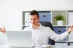L'homme d'affaires est fâché tout en travaillant sur l'ordinateur portable Photographie stock