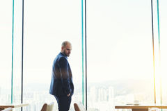 L'homme d'affaires est fenêtre proche debout de gratte-ciel avec le fond de l'espace de copie pour font de la publicité le messag Photos stock