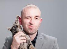 L'homme d'affaires est rayé par un chat au-dessus de fond gris Images stock