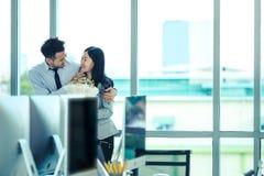 L'homme d'affaires et la femme d'affaires asiatiques est un flirt dans l'offi moderne photo libre de droits