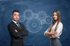 L'homme d'affaires et la femme d'affaires avec des roues de vitesse travaillent dans l'équipe sur le fond bleu Photos libres de droits