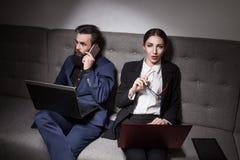L'homme d'affaires et la femme d'affaires se sont habillés dans le costume et avec l'ordinateur portable, p Image libre de droits