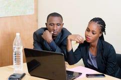 L'homme d'affaires et la femme d'affaires partagent un ordinateur portable Image stock