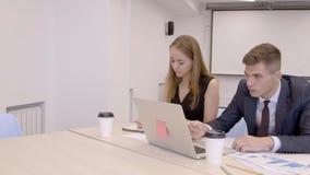 L'homme d'affaires et la femme d'affaires s'asseyent dans la chambre de Co-travail et établissent le rapport financier clips vidéos