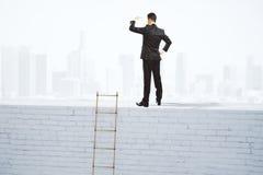 L'homme d'affaires examine la distance sur le dessus du wa blanc de brique images libres de droits