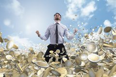 L'homme d'affaires exulte au-dessus de beaucoup de pièces de monnaie d'argent photos stock