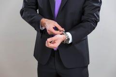 L'homme d'affaires ferme sa montre-bracelet Photographie stock libre de droits