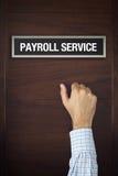 L'homme d'affaires frappe sur la porte de service de feuille de paie Photo stock