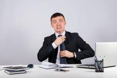 L'homme d'affaires frustrant crie et tire à son lien Images stock