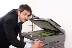 L'homme d'affaires gagnent l'argent faux sur la machine de copie photos libres de droits