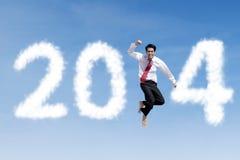 L'homme d'affaires heureux saute avec des nuages de 2014 Image libre de droits
