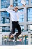L'homme d'affaires heureux saute dans le ciel Image stock