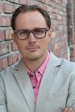 L'homme d'affaires imposant âgé dans le costume beige et la chemise habillée rose avec des bras ont croisé sur le coffre d'isolem Photographie stock libre de droits