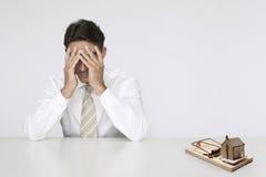 L'homme d'affaires inquiété à la maison modèle de table dans le piège de souris représentant les immobiliers chers coûte Images libres de droits