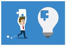 L'homme d'affaires insère le morceau absent avec l'ampoule Photo stock