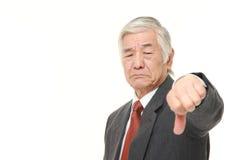 L'homme d'affaires japonais supérieur avec des pouces font des gestes vers le bas Photo stock